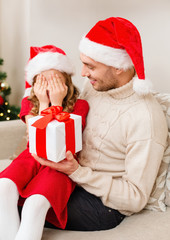 smiling daughter waiting for a present from father