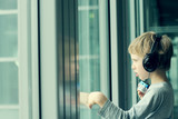 Fototapety boy with headphones looking out the window at the airport