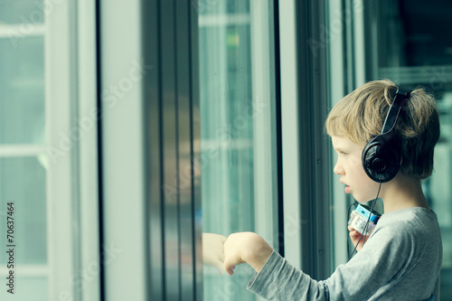 boy with headphones looking out the window at the airport - 70637464
