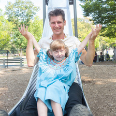 Father and Daughter Playing on Slide at Park