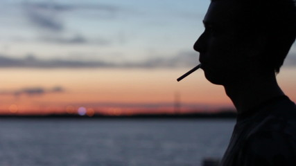 man smokes at the sunset