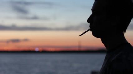 man smokes at the sunset