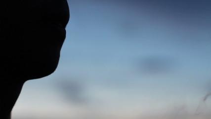 man smokes at the sunset close-up