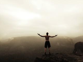 Naked man in pants. Sportsman on the peak of sandstone rock