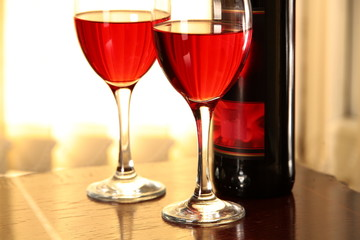 Close-up of glasses with red wine and bottle.