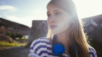 Teenage girl sitting with headphones around neck