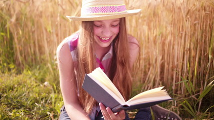 Young Girl Reading Next to Wheat Field