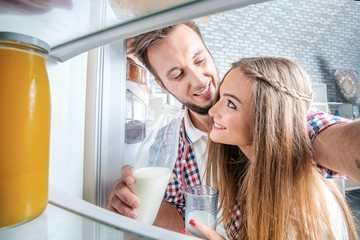 Look in the fridge. Young and successful couple in love looks in