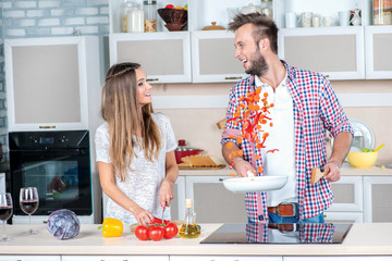 A cheerful joint cooking. Young and beautiful couple in love pre