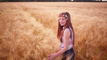 Young girl having a good time walking through wheat fields