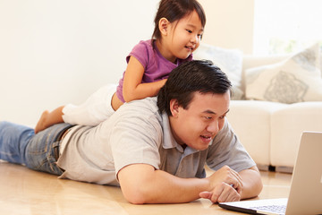 Father And Daughter Watching Movie On Laptop At Home