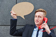 Geschäftsmann hält Sprechblase beim Telefonieren