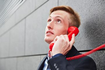Geschäftsmann telefoniert mit rotem Telefon