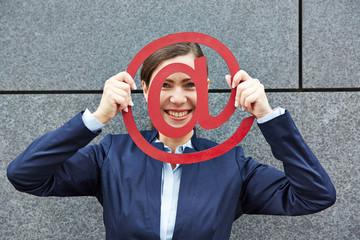 Lächelnde Frau schaut durch at-Zeichen