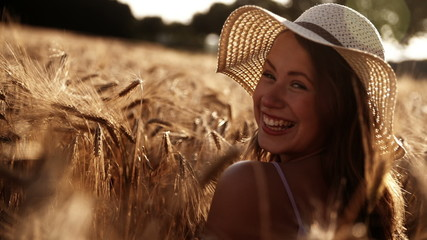 Girl looking over shoulder and laughing in wheat field