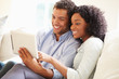 Young Couple Sitting On Sofa Using Digital Tablet - 70644096