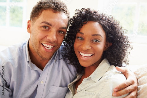 canvas print picture Portrait Of Young Couple Sitting On Sofa At Home