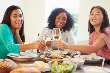 Group Of Female Friends Enjoying Meal At Home