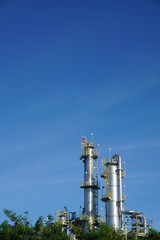 Petrochemical factory and green nature on blue sky backgound