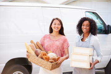 Female Bakers With Bread And Cakes Standing In Front Of Van