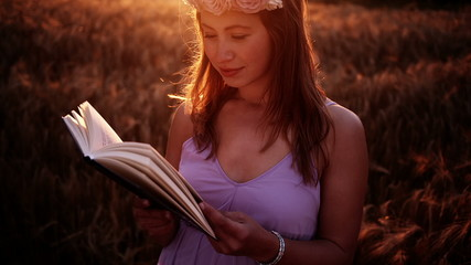Girl with flower crown reading a book at sunset