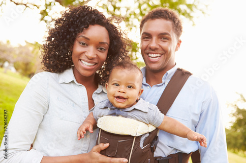 canvas print picture Family With Baby Son In Carrier Walking Through Park
