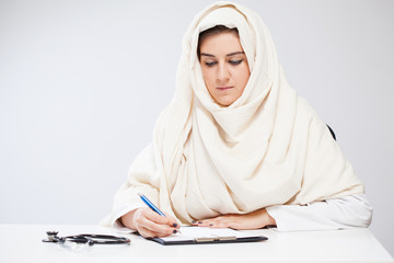 Muslim lady doctor writing documents