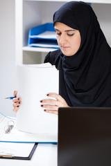 Muslim female office worker doing paperwork