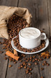 Coffee cup with cinnamon sticks and coffee bag on wooden table
