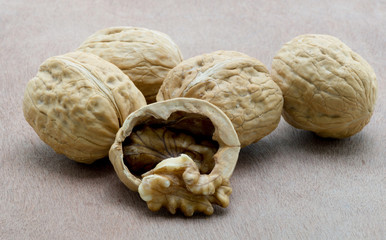 Walnut kernels and whole walnuts on wooden surface