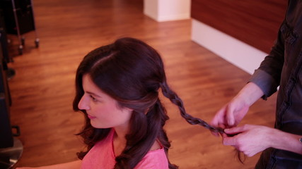 Hair stylist making plait in woman's hair