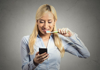 business woman reading news on smartphone brushing teeth