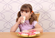 little girl with sweet donuts and milk breakfast