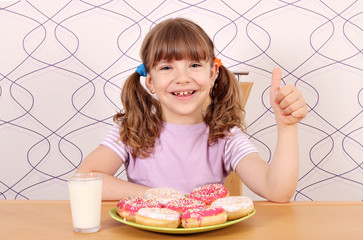 happy little girl with thumb up and donuts for breakfast