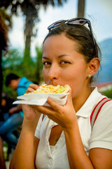 beautiful young girl eating a tostada soft taco