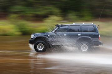Большой черный внедорожник быстро едет по мокрой дороге