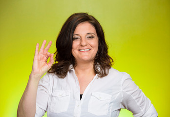 excited woman giving OK sign on green background