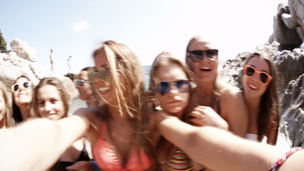 Group of girl friends taking selfie at the beach