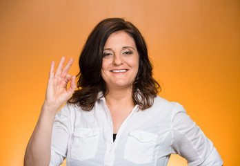 excited woman giving OK sign on orange background