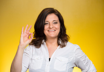 excited woman giving OK sign on yellow background