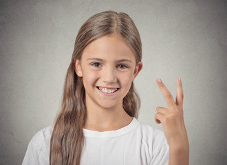 Headshot happy teenager girl giving number two, victory sign