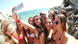 Group of girl friends taking selfie at the beach in slow motion