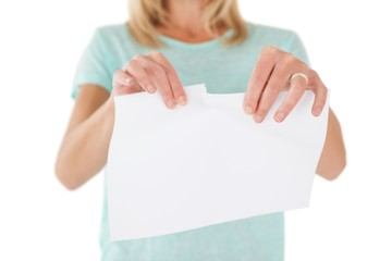 Mid section of woman holding torn sheet of paper