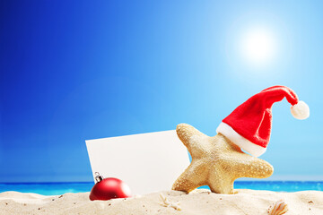Starfish with Santa hat and paper stuck on beach