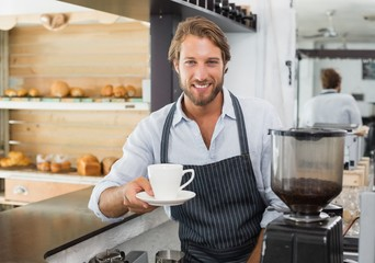 Handsome barista offering a cup of coffee to camera