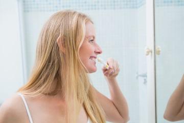 Happy woman brushing her teeth