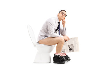 Pensive man sitting on toilet and holding a paper