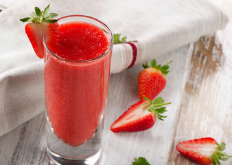 Strawberry smoothie with fresh berries on a wooden background