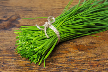 a bunch of fresh chives on a wooden table