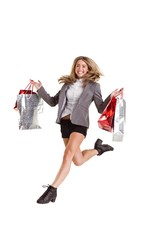 Stylish blonde jumping with shopping bags